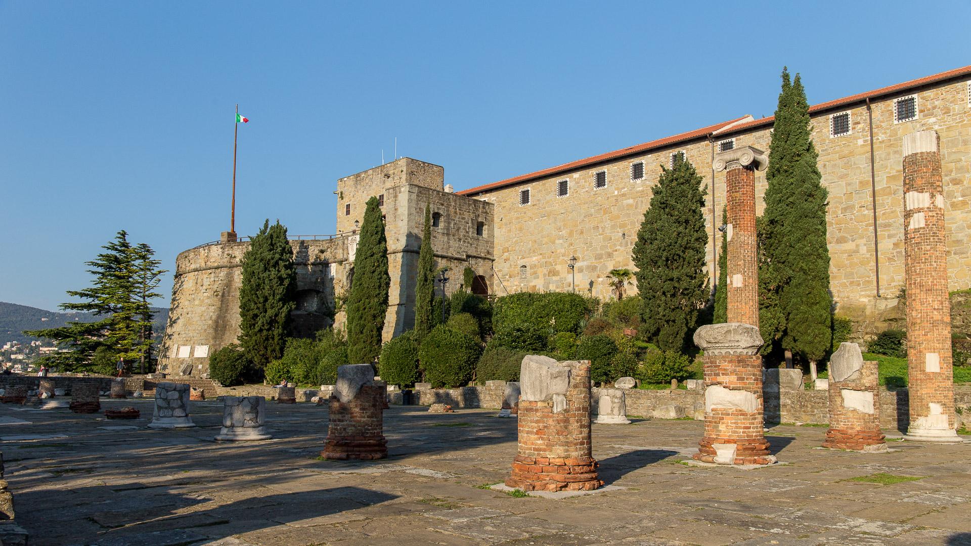 Überreste der römischen Basilika und die Festung San Giusto im dahinter